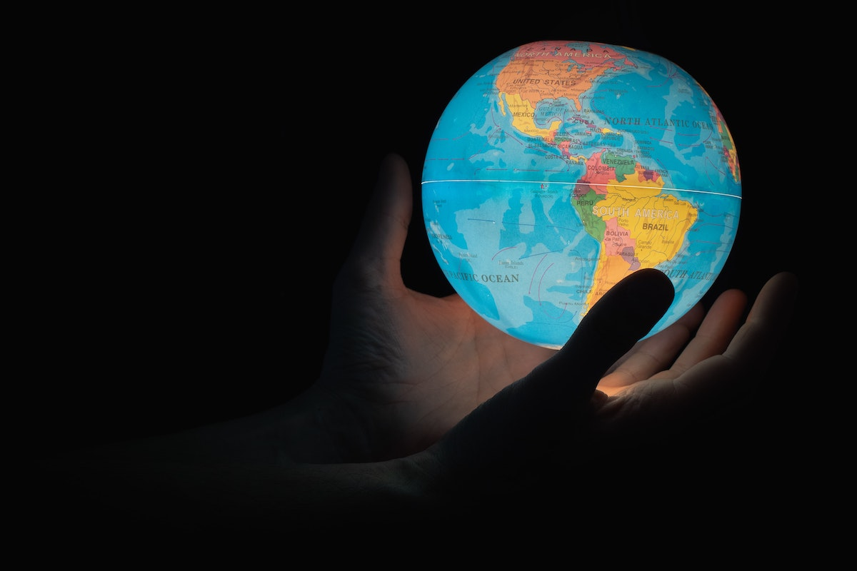Image of a lighted globe and hands